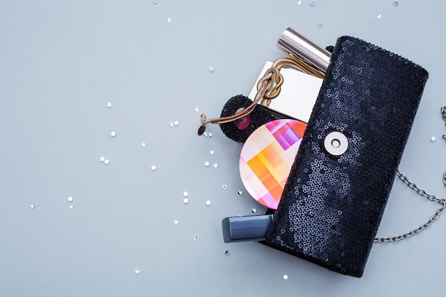 灰色の背景上の化粧品と女性のハンドバッグ