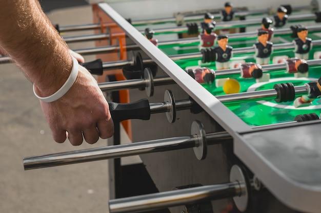サッカーテーブルサッカーゲームレクリエーションレジャーを楽しんで遊ぶ人々