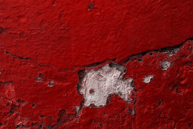 赤い色の剥離ペイントでコンクリートの石の壁のテクスチャグランジ背景