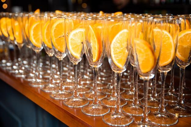 多くの空のグラスがガラスの上に立っており、ガラスの内側にはオレンジのスライスがあります。メガネは木製のテーブルの上に立ちます。