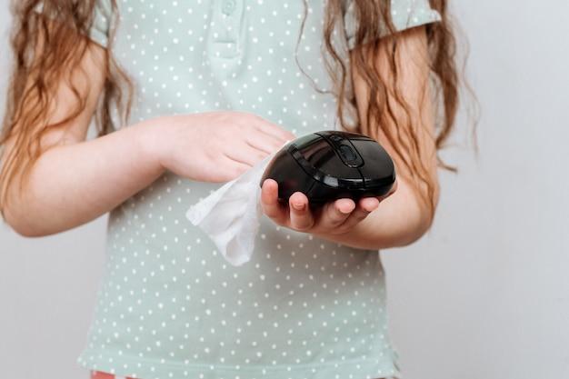 女の子は、消毒用ワイプでコンピューターのマウスを拭きます。