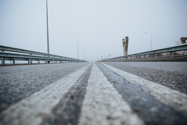 道路の分割線は、舗装された道路を下から見下ろすと白く見えます。路上のアスファルトの道路標示。
