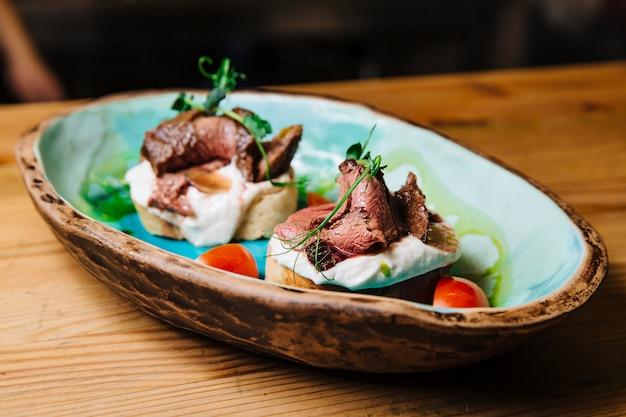 オニオンブレッドミディアムレアローストビーフにローストビーフとサワークリームベースのソースを添えたブルスケッタ。
