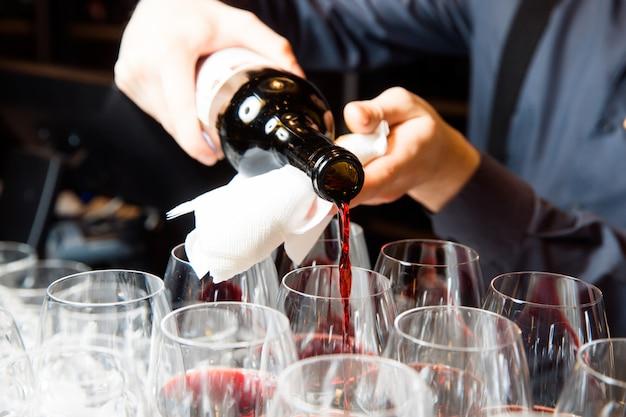 Официант наливает красное вино в бокалы.