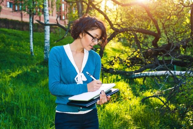 ノートブックで若い学生。屋外でのオンライン学習。