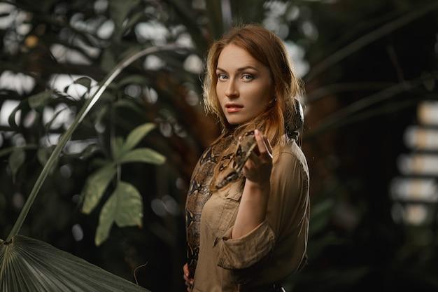 Красивая девушка с естественным макияжем и рыжими волосами стоит в джунглях среди экзотических растений со змеей.