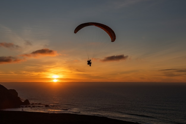 Параплан пролетел над берегом теса на закате. парапланеризм спорт