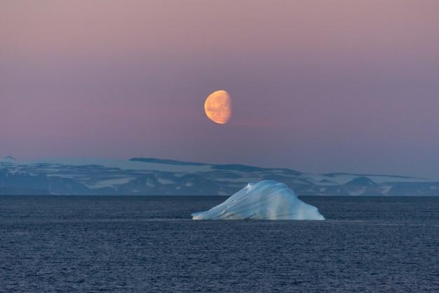Красивый восход луны в гренландии. айсберг на море.