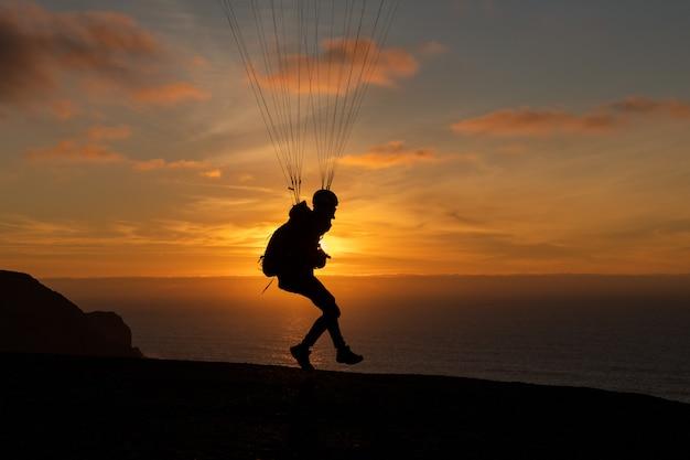 夕暮れ時のテセア海岸上空を飛ぶパラグライダー。パラグライダースポーツ
