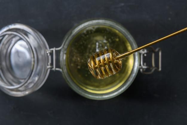 金属の蜂蜜ディッパーと蜂蜜でいっぱいのガラス瓶