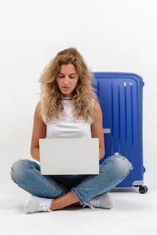 ノートパソコンと白い壁にスーツケースと美しい若い女性