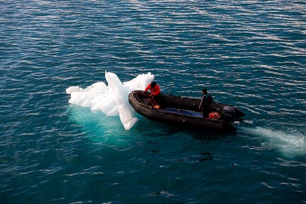 北極海、スバールバル諸島で一人で膨脹可能なボート。氷を押します。