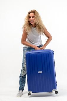 白い壁に青いプラスチックのスーツケースと美しい若いブロンドの女性