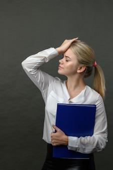 灰色の背景にストレスと頭痛のある青いフォルダーを保持している若い美しいブロンドの女性。頭痛を持つ若いきれいな女性。