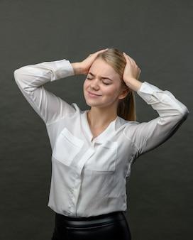 ストレスと灰色の背景に頭痛の種の若い美しいブロンドの女性。頭痛のきれいな女性。