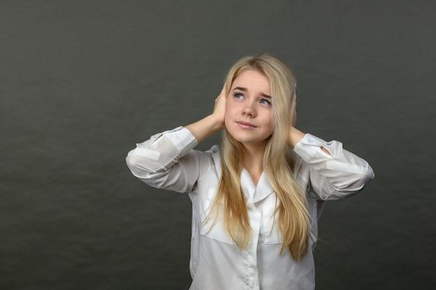 ストレスと灰色の背景に頭痛の種の若い美しいブロンドの女性。彼女の頭を保持している女性。頭痛のきれいな女性。