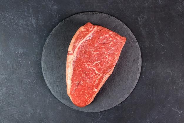 暗い背景の上面に生の新鮮な霜降り肉