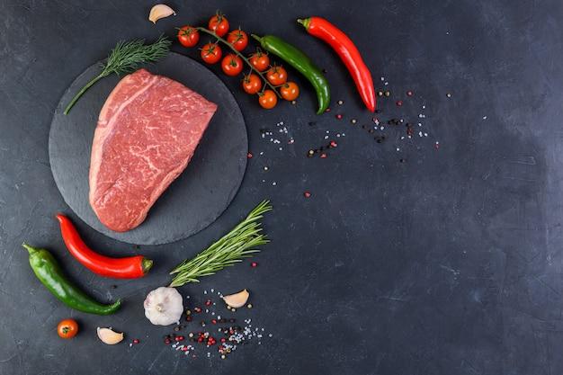 生の新鮮な霜降り肉と暗い背景の上に調味料を争う