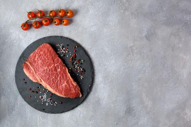 生の新鮮な霜降り肉と灰色の背景の上に調味料を争う