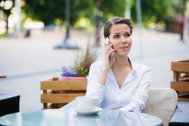 コーヒーを飲みながら彼女の携帯電話を使用して話している屋外カフェで座っている若いビジネス女性の肖像画