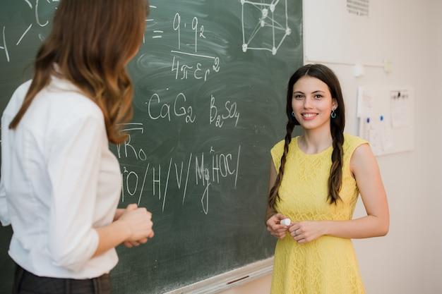 Девочка отвечает на вопросы учителей у школьной доски