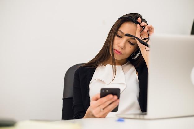 Скучающая женщина за столом печатает сообщение на мобильном телефоне