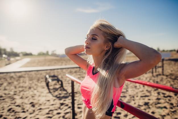 Красивая женщина спортсмена делая спорт работая на пляже