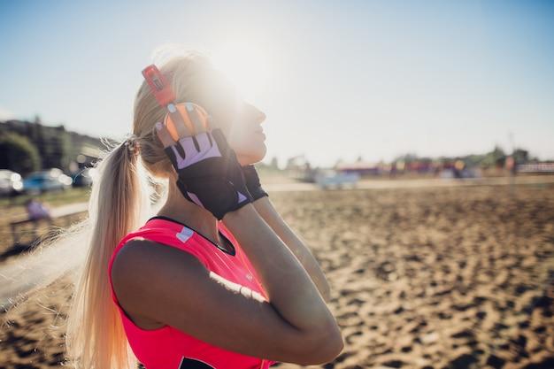 ビーチでヘッドフォンで音楽を聴くピンクのカラフルなスポーツスーツの美しい若いブロンドの女性のスポーツ屋外写真