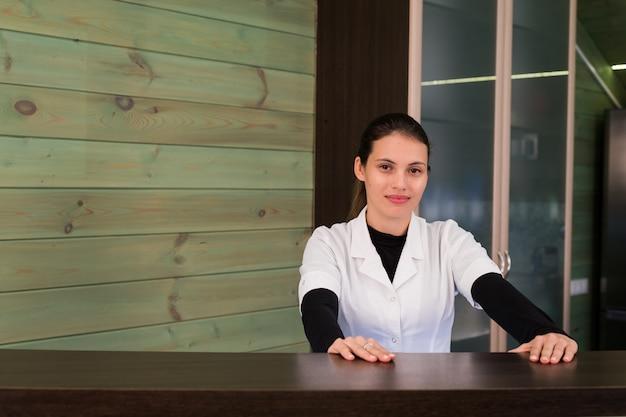 受容の女性は笑顔で、スパや近代的な診療所で仮想訪問者を歓迎します。あなたの手に同意のある論文。