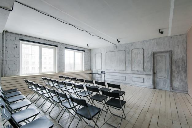 Комната для лекций с множеством темных стульев. стены белые, лофт интерьер. справа есть дверь.