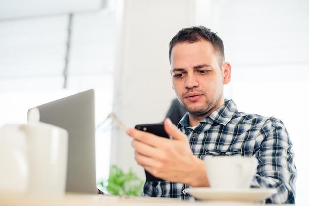 Портрет крупным планом, подчеркнутый молодой человек в фиолетовом свитере, удивленный, испуганный и встревоженный тем, что он видит на своем мобильном телефоне