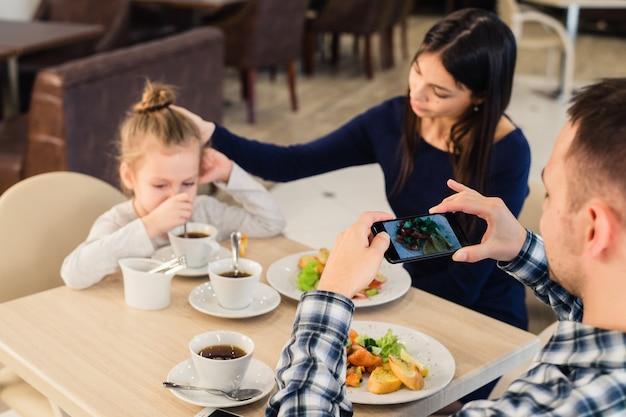 レジャー、技術、ライフスタイル、人々の概念。スマートフォンでレストランで料理の写真を撮ると幸せな家庭