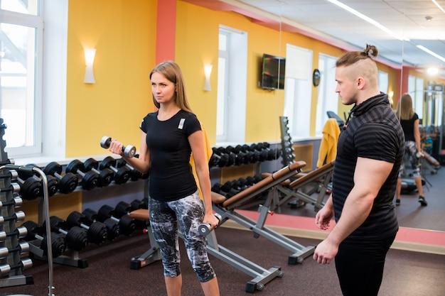 Женщина с ее личным тренером по фитнесу в тренажерном зале, осуществляющих силовую гимнастику со штангой