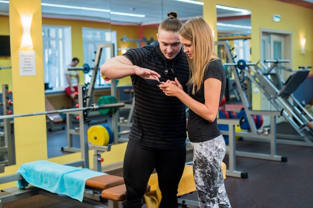 Фитнес, спорт, физические упражнения, технологии и диета концепции. улыбающаяся молодая женщина и личный тренер со смартфоном в тренажерном зале