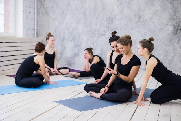 Группа счастливых девушек в фитнес-классе на перерыв, глядя на смартфон