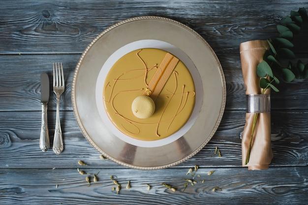Свежеиспеченный желтый пудинг с миндальным даккуазом, малиновым конфитом, хрустящим слоем с карамелизированным фундуком и малиновым порошком