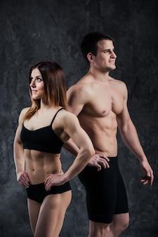 暗い背景にフィットネススポーティな健康的なカップルの男女