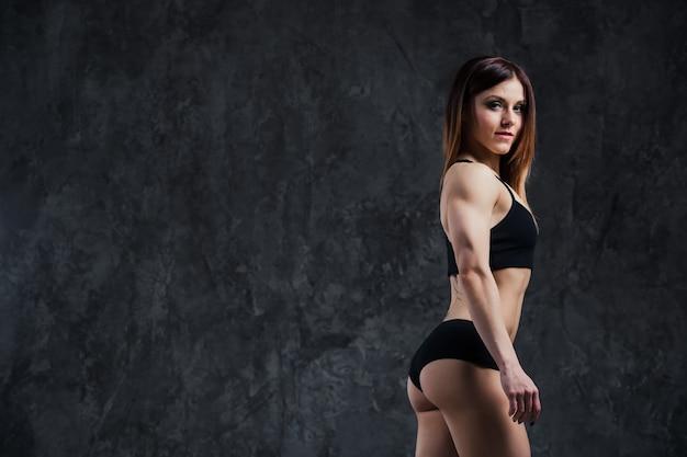 ジムでトレーニングしている汗のビーズを持つ若い美しいフィットネス女性の裏側の暗いコントラスト写真。