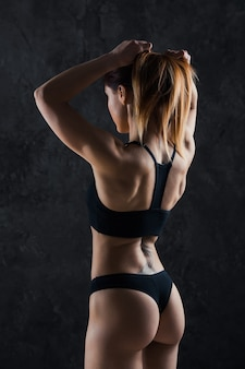 Молодая девушка фитнеса готовя для разминки изолированной на темноте