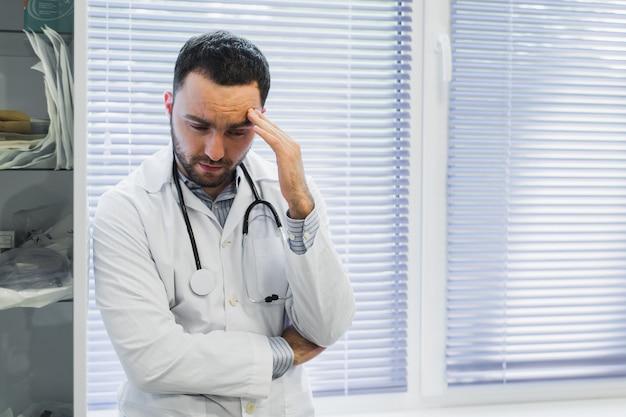 Серьезный мужской доктор держит его стетоскоп и стоит с оружиями сложил в его офисе смотря взгляд с угрозой.