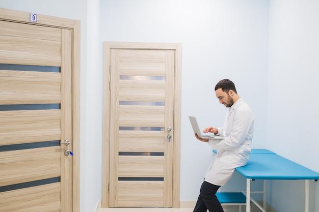 Врач-специалист в коридоре своей клиники со своим ноутбуком