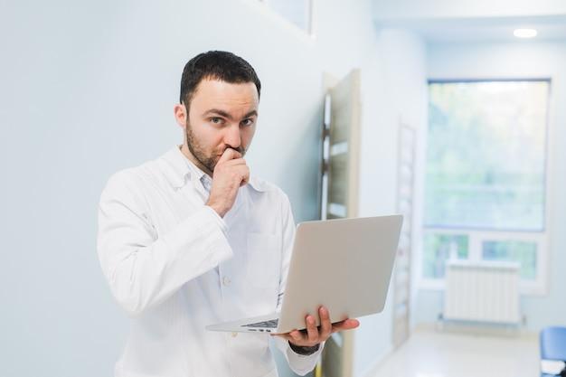 成功した医師が自分のオフィスに立ち、ラップトップを使用して仕事をしている
