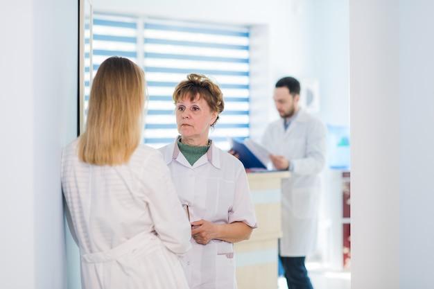 Зрелый доктор обсуждая с медсестрами в прихожей больницы. доктор обсуждает состояние пациента с его медицинским персоналом после операции.