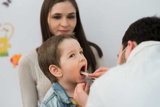 Маленький мальчик с его горлом осмотрен медицинским работником