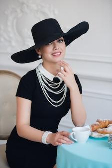 有名な女優、クロワッサンがお茶を食べたり飲んだりするような帽子の女。