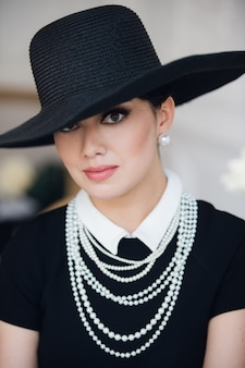 黒のドレス、帽子、真珠を着て、椅子に座って魅力的な女性