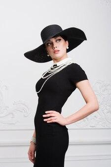 Портрет красивой молодой женщины в стиле ретро в элегантной черной шляпе и платье над роскошной стеной рококо