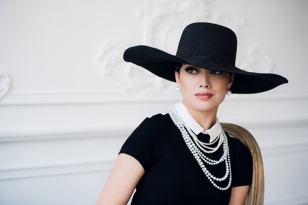 エレガントな黒い帽子と豪華なロココ様式の壁の上のドレスでレトロなスタイルの美しい若い女性の肖像画