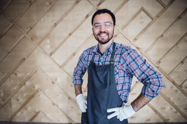 若い男性大工の手袋を着用し、腰に手でメガネ