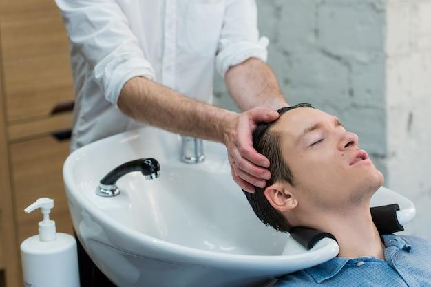 Молодой человек в парикмахерской, мыть волосы